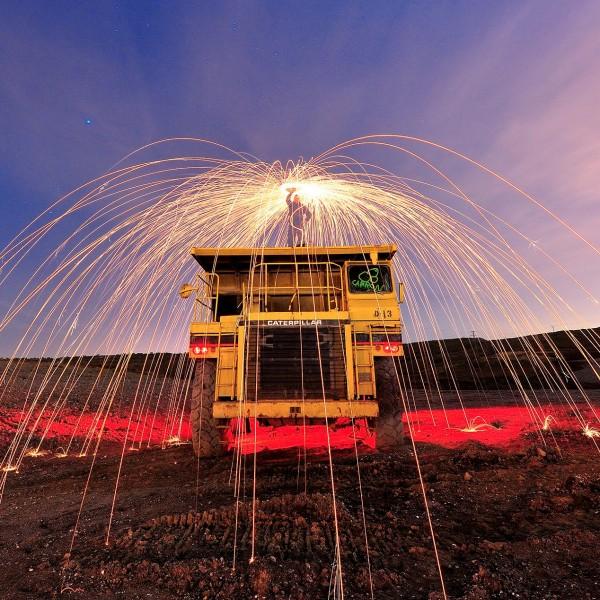 Fotografía nocturna de pintura con luz, con lana de acero sobre máquina agrícola.
