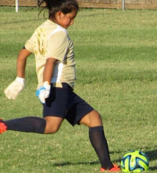 niña en campo de futbol jugando como portera