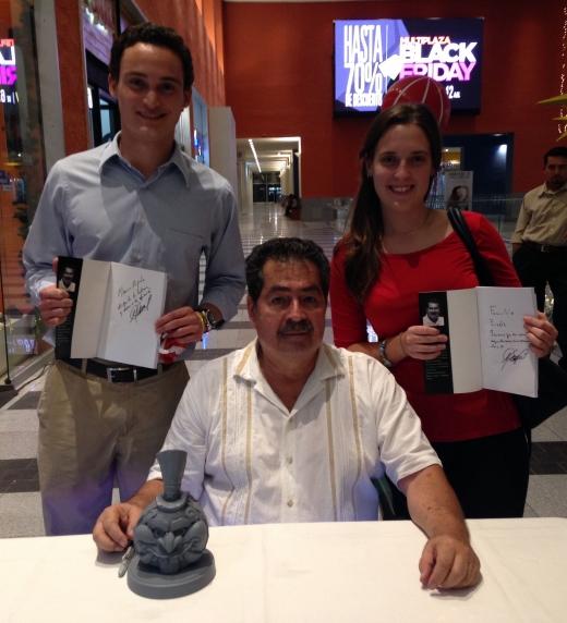 """Ernesto Panama junto a amigos que adquieren su obra.  Sobre la mesa la escultura que se presenta en la portada obra de: Oscar """"KEIN"""" Cornejo, Ilustrador."""