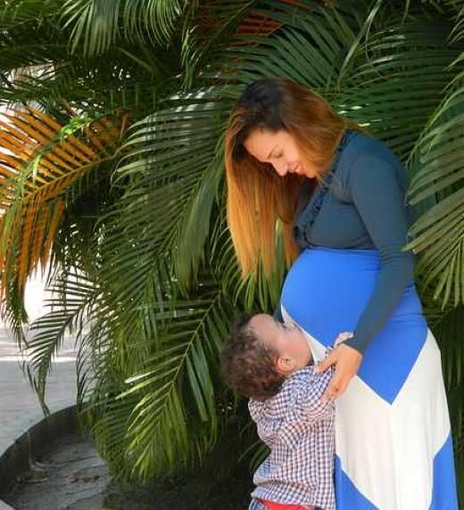 Mamá embarazada jugando con uno de sus hijos.