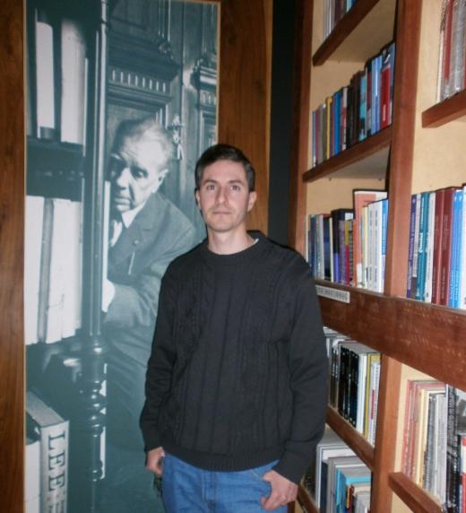 Eliseo Monteros rodeado de libros. Al final, un retrato de Borges, uno de los escritores mencionados en el libro Un lector agradecido.