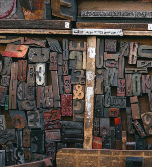 Distintos tipos móviles (de caja alta, caja baja, números, signos ortográficos, ornamentos, etc.) sobre un chibalete o caja de tipografía.