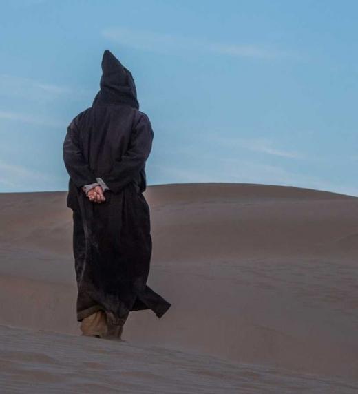 Beduino caminando por las dunas.
