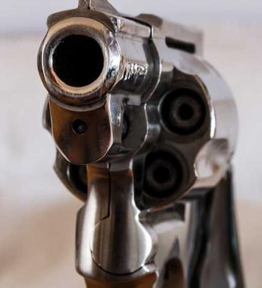 Revólver apuntando al observador. Representa asesinatos en el libro. Delitos, policíaca.