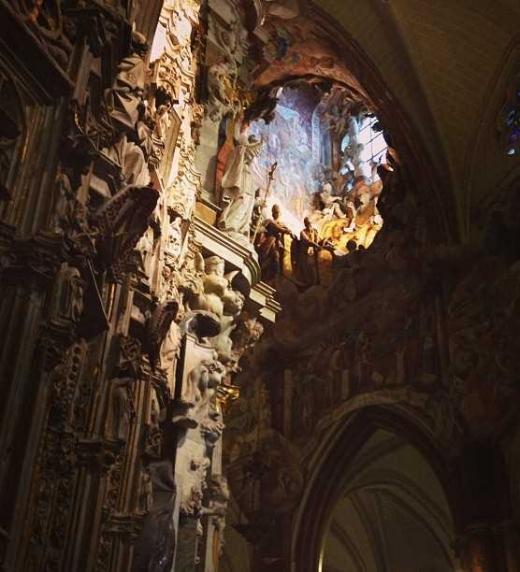 Ventanal de la Catedral de Toledo. La luz ilumina el pilar principal con relieves religiosos.