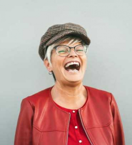 Mujer de más de 40 años riendo a carcajadas