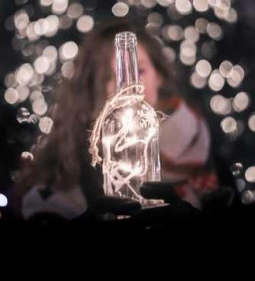 Mujer sosteniendo una botella con luces en el interior.