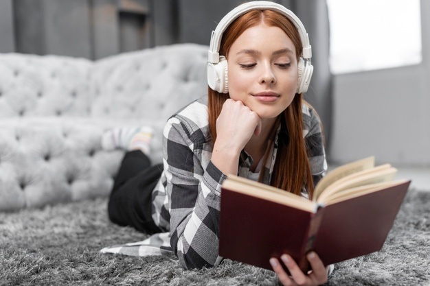 Chica leyendo libro y escuchando música